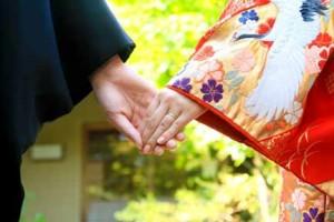 結婚式で手をつなぐ成婚カップル