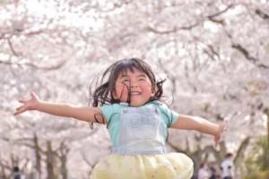 桜吹雪の中を走り回る女の子