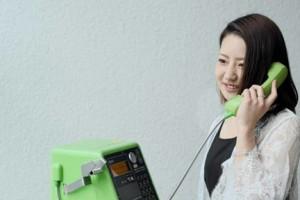 公衆電話から相談室に電話する女性会員