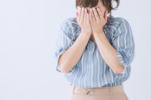泣き顔を両手で隠す女性