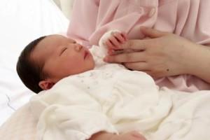 母の手を握る出産後の赤ちゃん