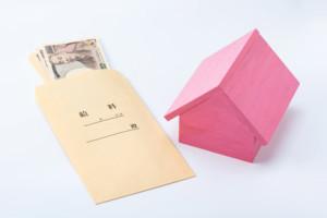 家賃支払いのイメージ(給料袋と家の模型)